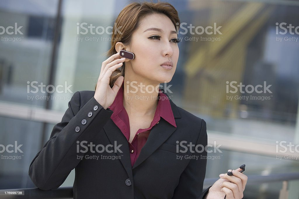 Young woman using bluetooth headset royalty-free stock photo
