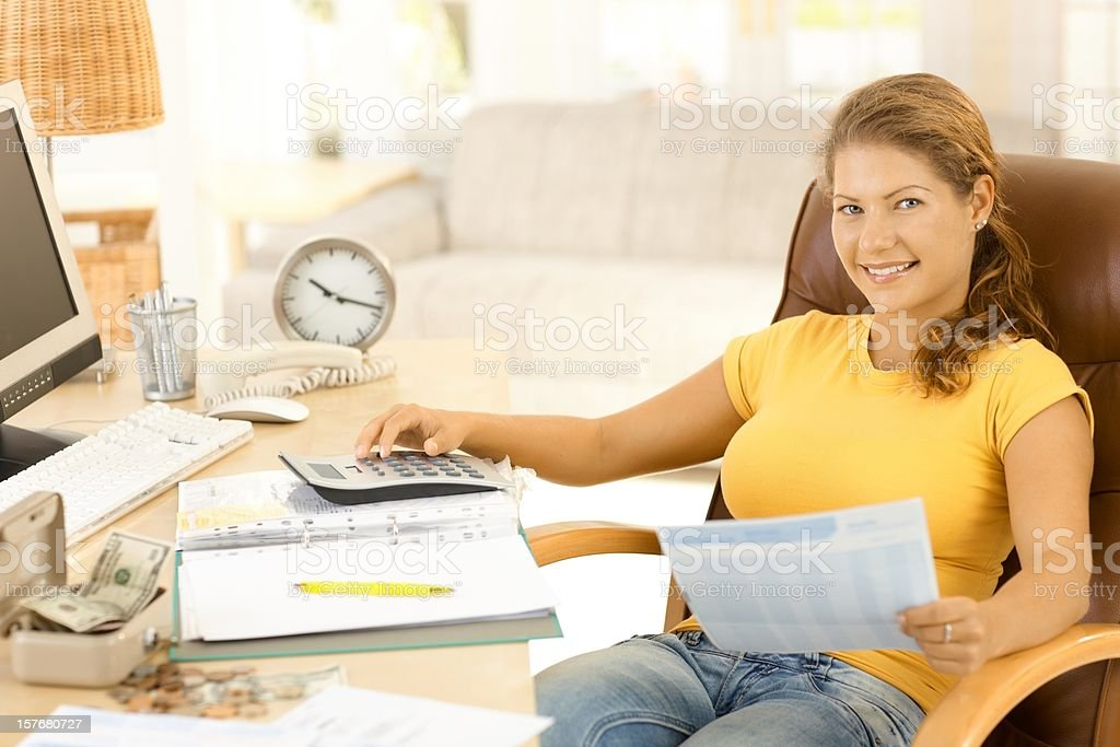Young woman using calculator at home royalty-free stock photo