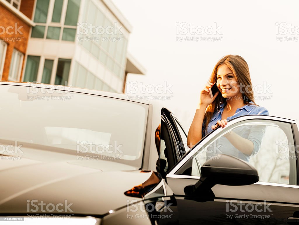 Young woman using cell phone and driving new car stock photo