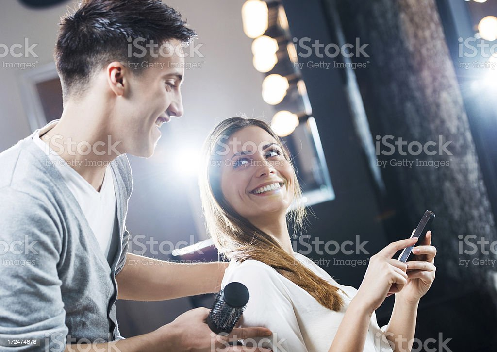 Young woman using cell phone while at hairdresser's. royalty-free stock photo