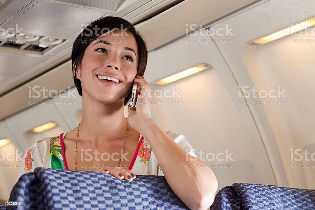 Young woman using cellphone on airplane royalty-free stock photo