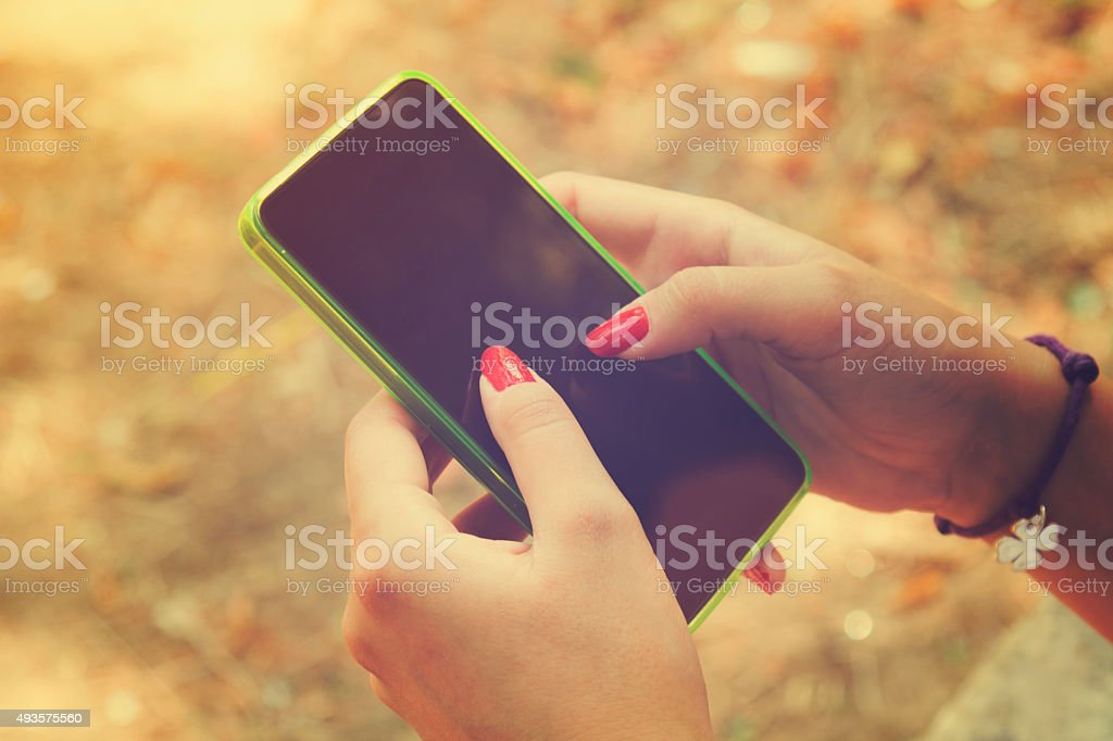 Young woman using cellphone outdoors. stock photo