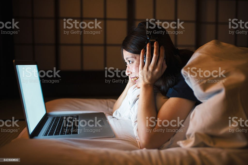 Young woman using computer in bed stock photo