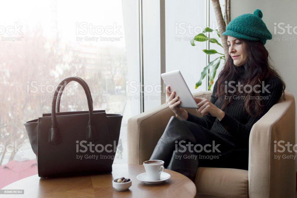 Young woman using digital tablet at cafe stock photo