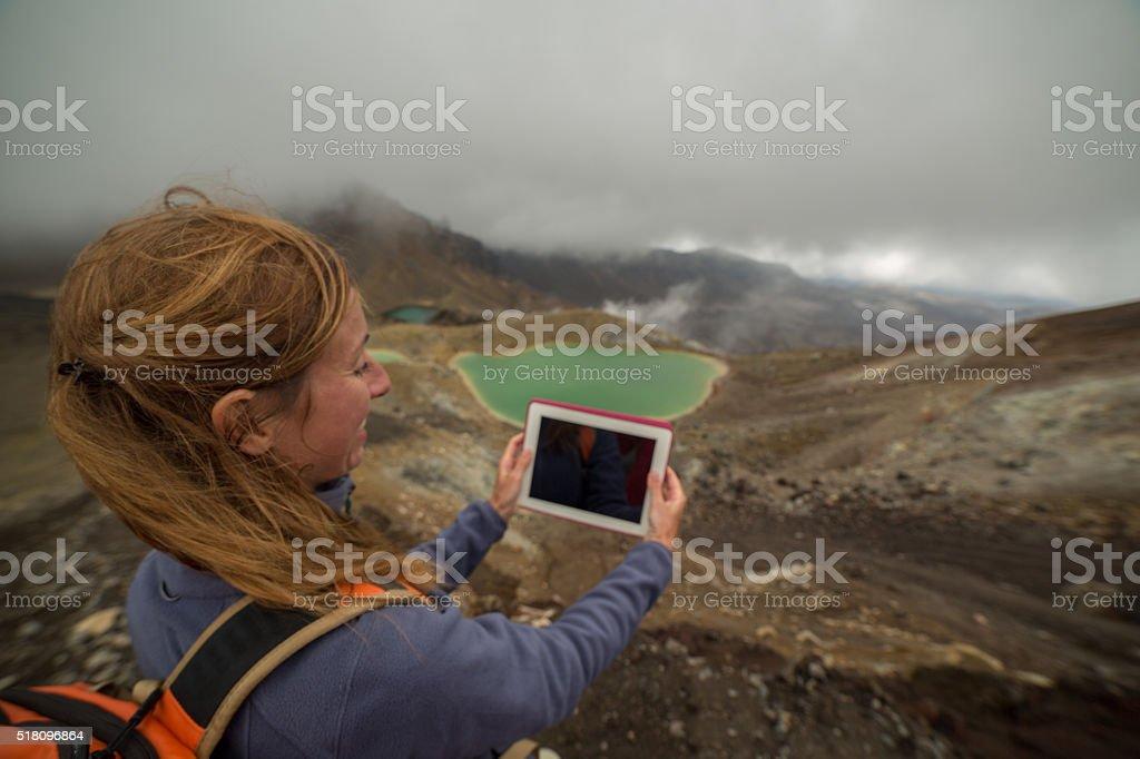 Young woman using digital tablet at Emerald lakes, Tongariro-NZ stock photo