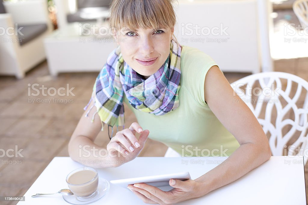 Young Woman Using Digital Tablet In Cafe royalty-free stock photo