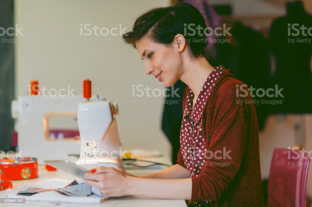 Young Woman Using Digital Tablet In Her Tailor Shop. stock photo