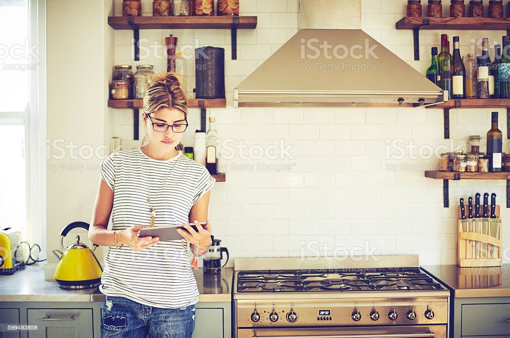Young woman using digital tablet in kitchen stock photo