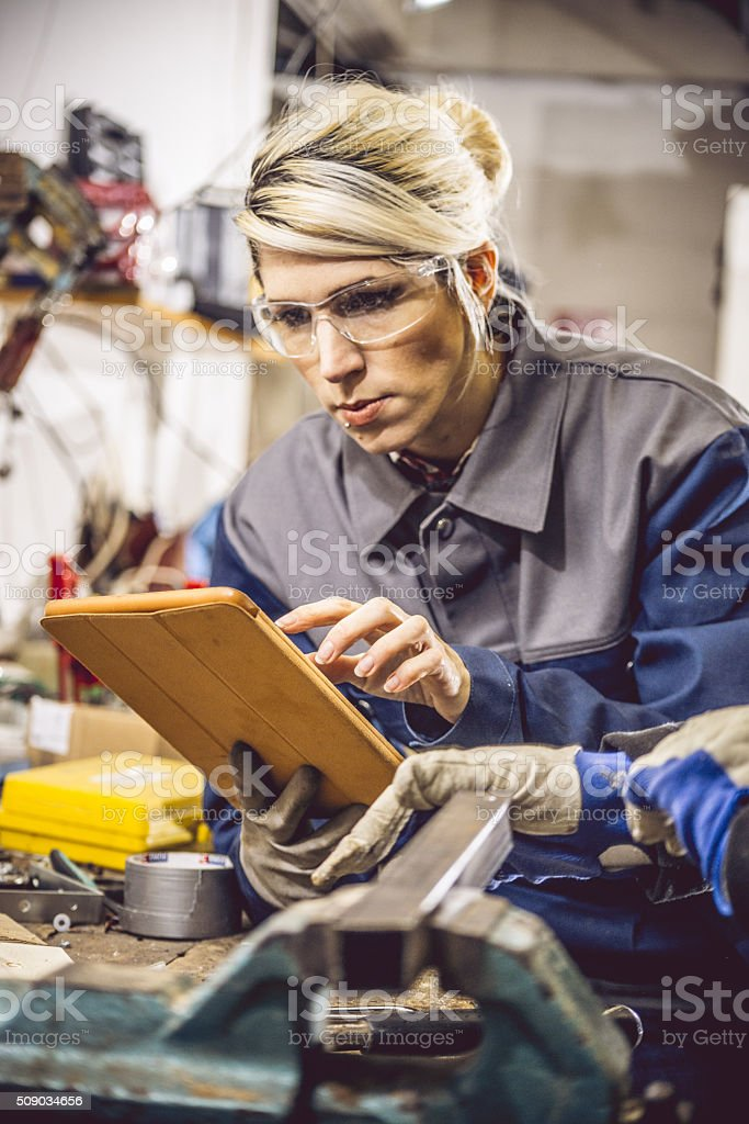 Young Woman Using Digital Tablet in Mechanical Workshop stock photo