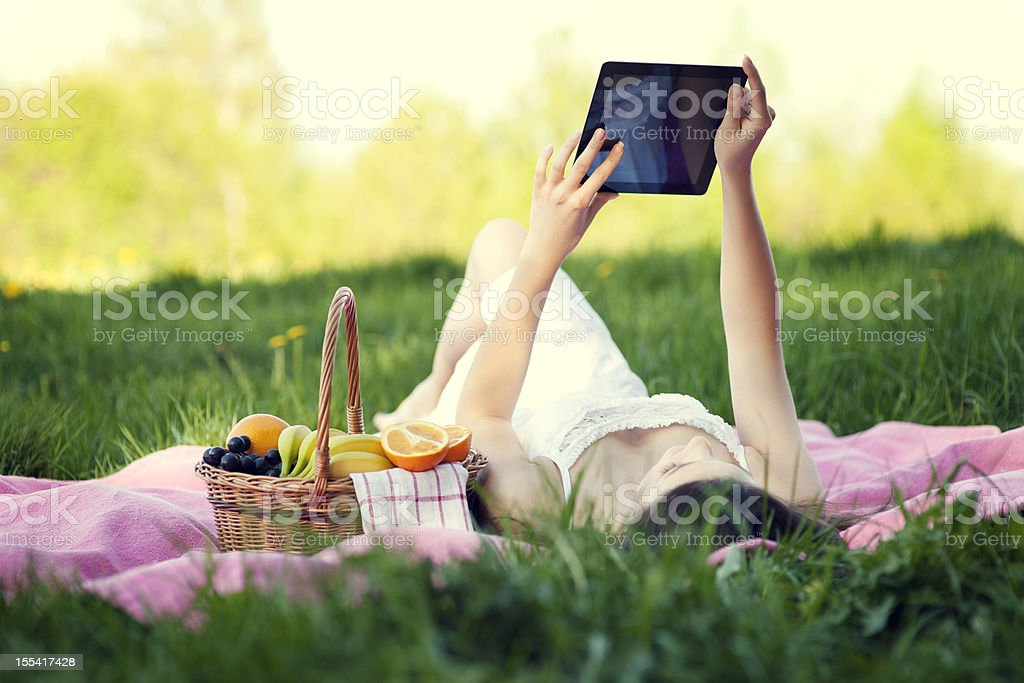 Young woman using digital tablet on meadow royalty-free stock photo