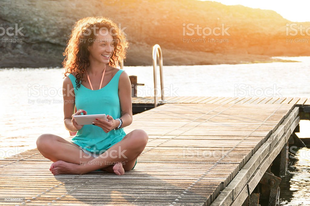 Young woman using digital tablet sitting on the pier stock photo
