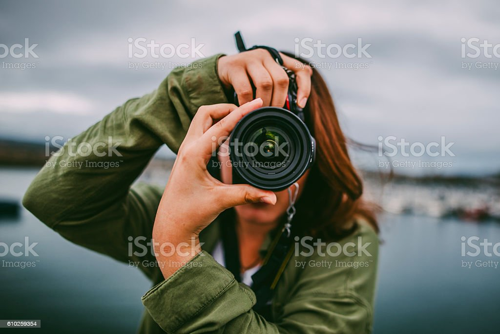 Young woman using DSLR camera stock photo