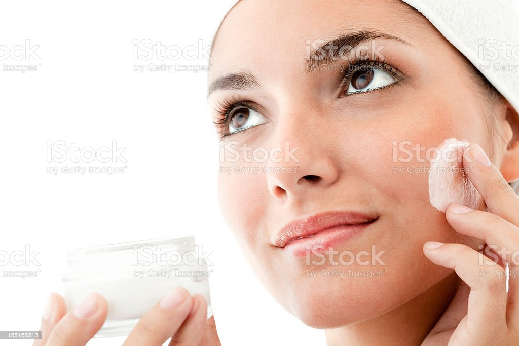 Young Woman Using Facial Cream - Isolated royalty-free stock photo