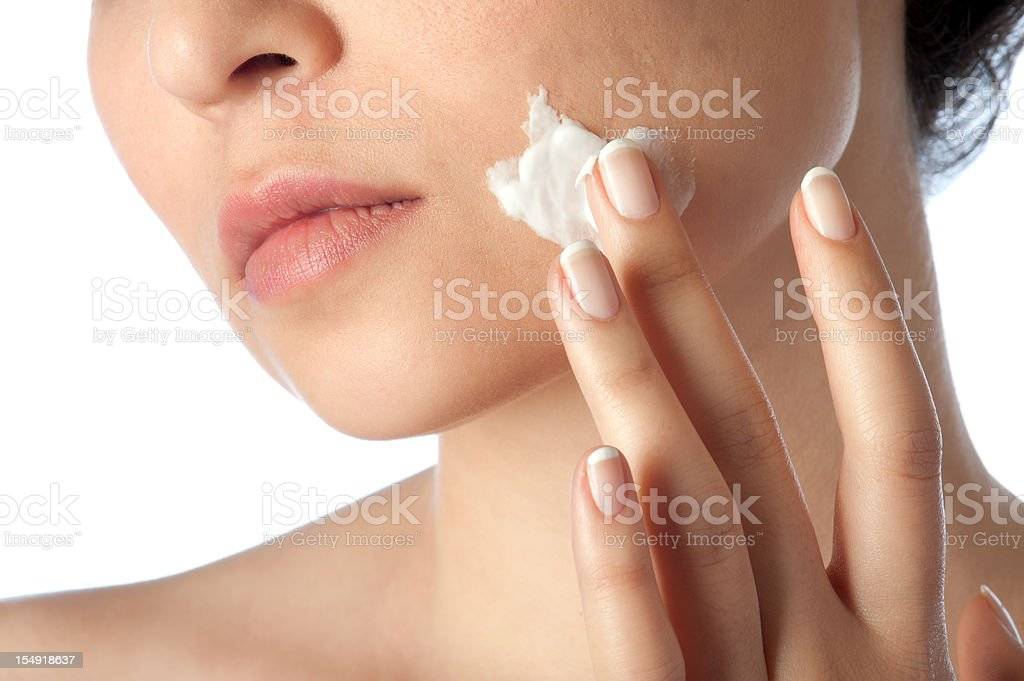 young woman using facial creme royalty-free stock photo