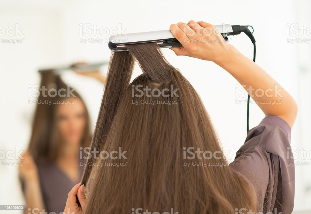 young woman using hair straightener in bathroom. rear view stock photo