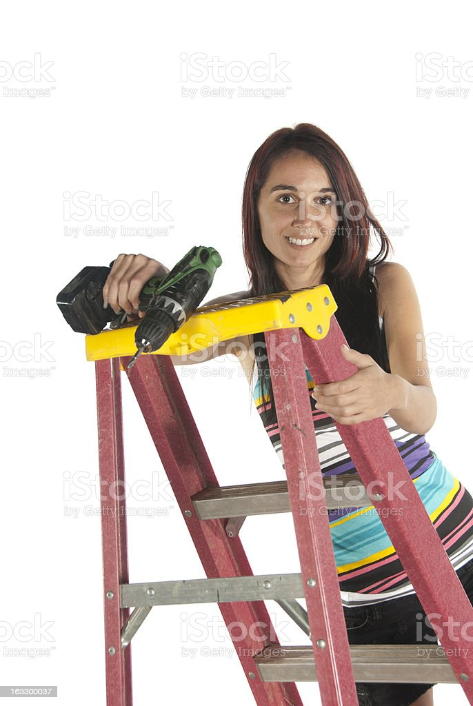 Young woman using hand dril tool and step ladder royalty-free stock photo