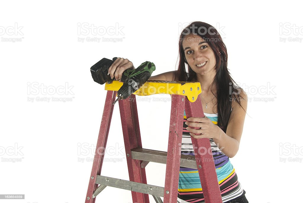 Young woman using hand drill and step ladder royalty-free stock photo