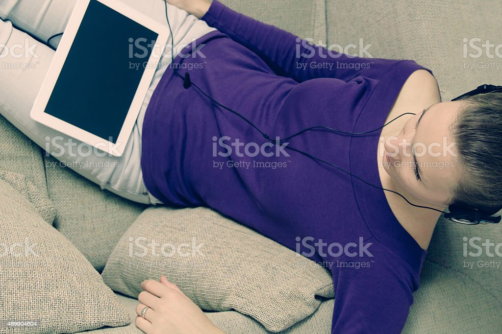 Young woman using headphones digital tablet at home stock photo
