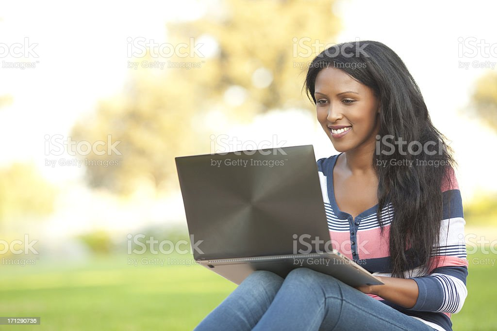 Young woman using her laptop at the park stock photo