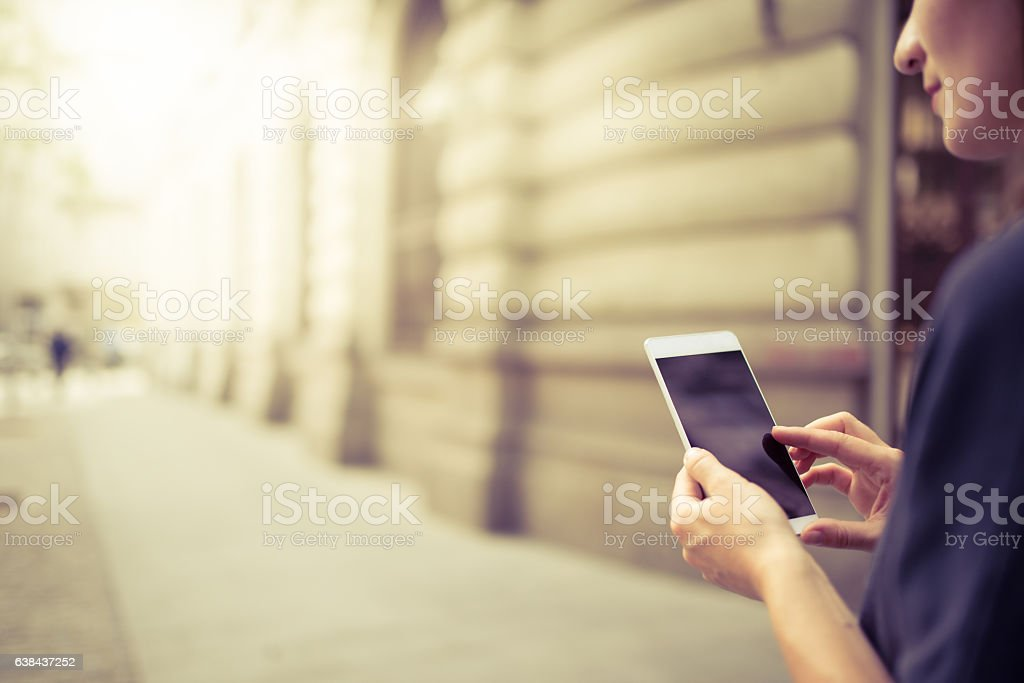 Young woman using her Mobile Phone on the street stock photo