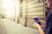 Young woman using her Mobile Phone on the street