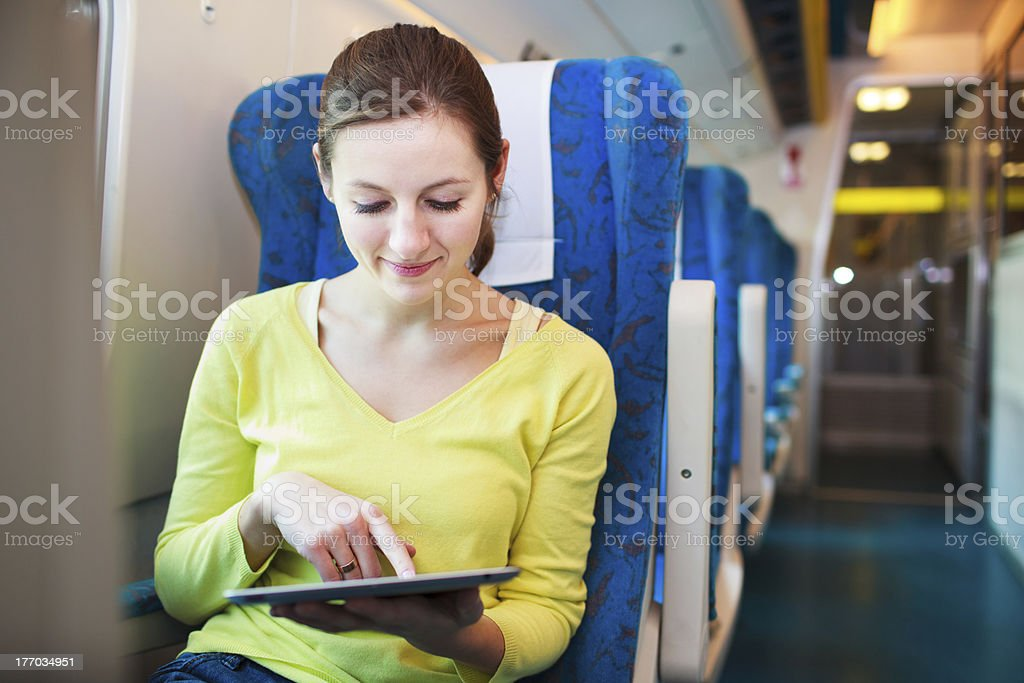 Young woman using her tablet computer while traveling by train royalty-free stock photo