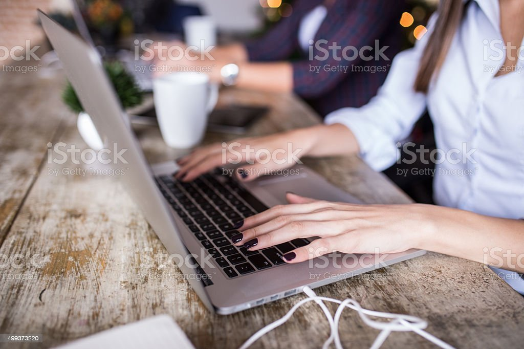 Young woman using laptop at home office. Modern office interior, stock photo