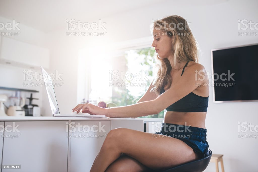 Young woman using laptop computer in the kitchen stock photo