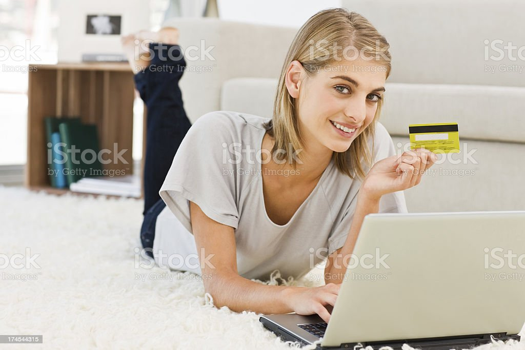 Young woman using laptop holding credit card royalty-free stock photo