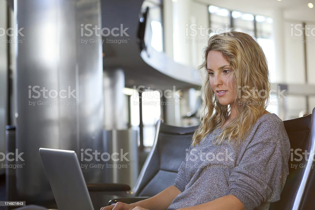 Young woman using laptop in airport terminal royalty-free stock photo
