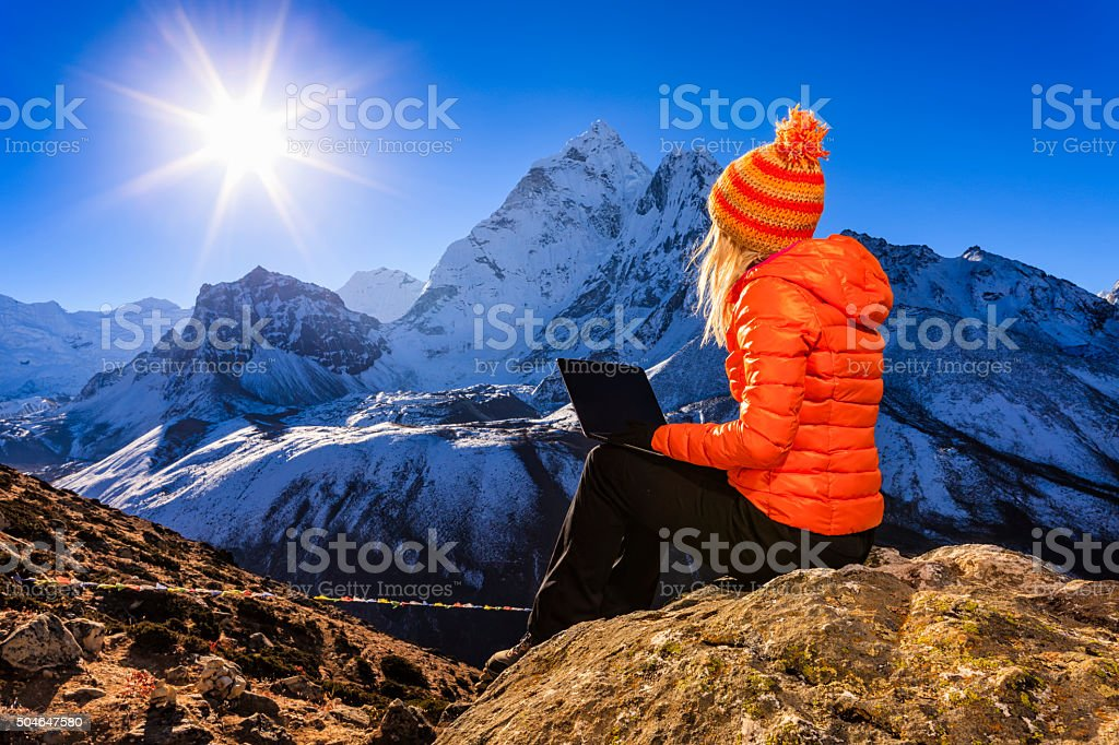 Young woman using laptop in Himalayas, Nepal stock photo