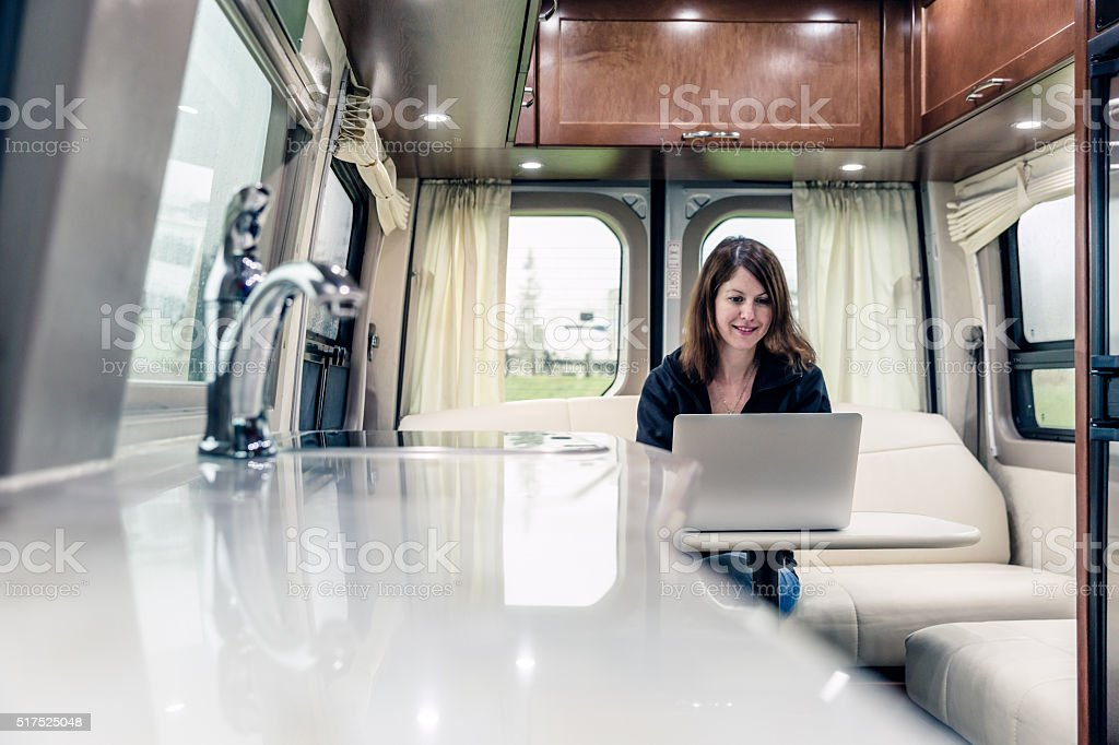 Young Woman Using Laptop Inside Motorhome stock photo