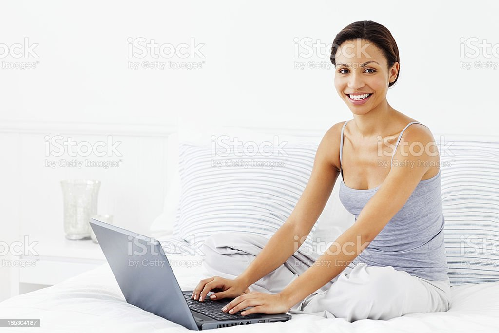 Young Woman Using Laptop on Her Bed royalty-free stock photo