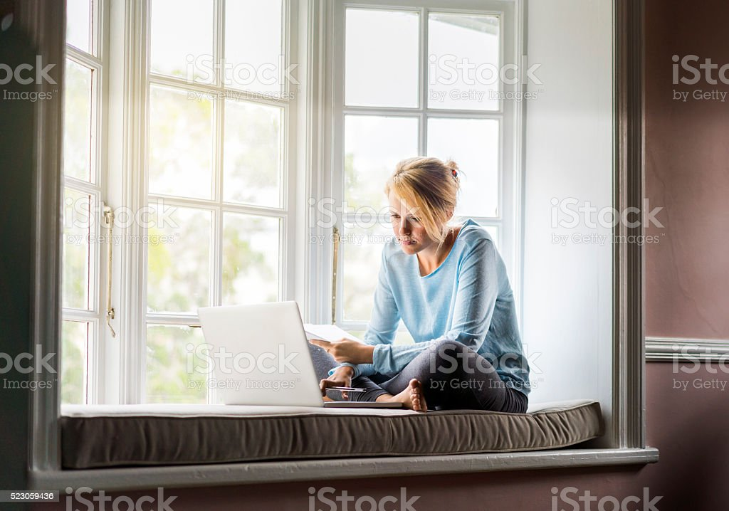 Young Woman using laptop on window sill stock photo