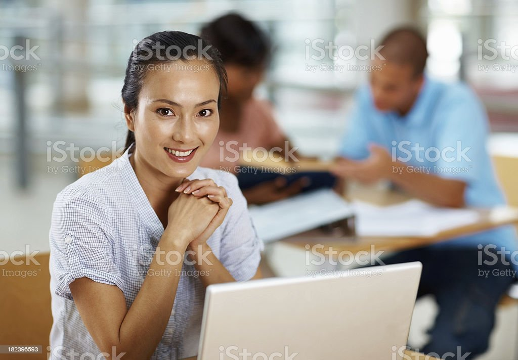 Young woman using laptop with friends at the back royalty-free stock photo