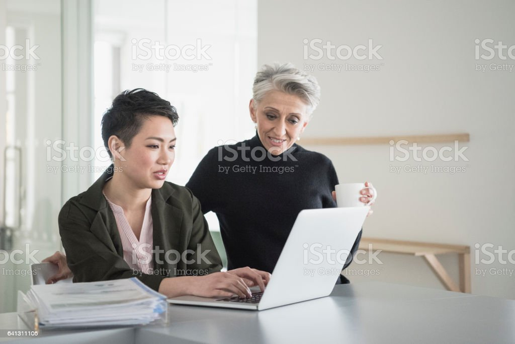 Young woman using laptop with senior manager looking at monitor stock photo