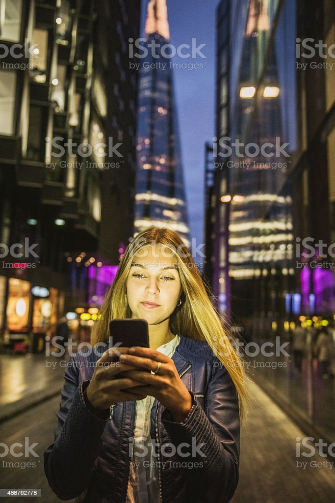 Young woman using mobile app on smartphone at night stock photo