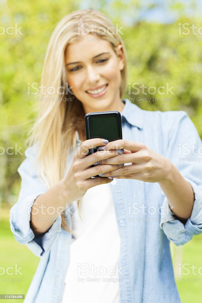 Young Woman Using Mobile Phone At Park royalty-free stock photo
