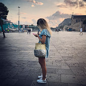 Young woman using mobile phone in Port Vell, Barcelona