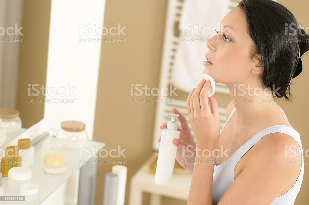 Young woman using product to clean face in a bathroom stock photo