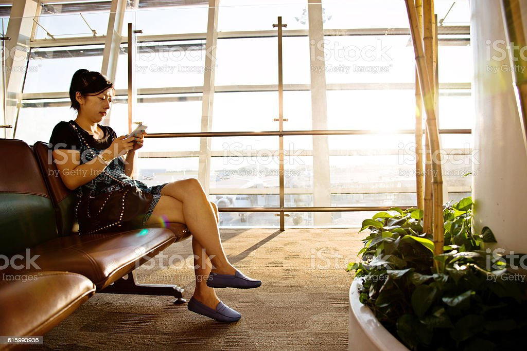 Young woman using smart phone at airport stock photo
