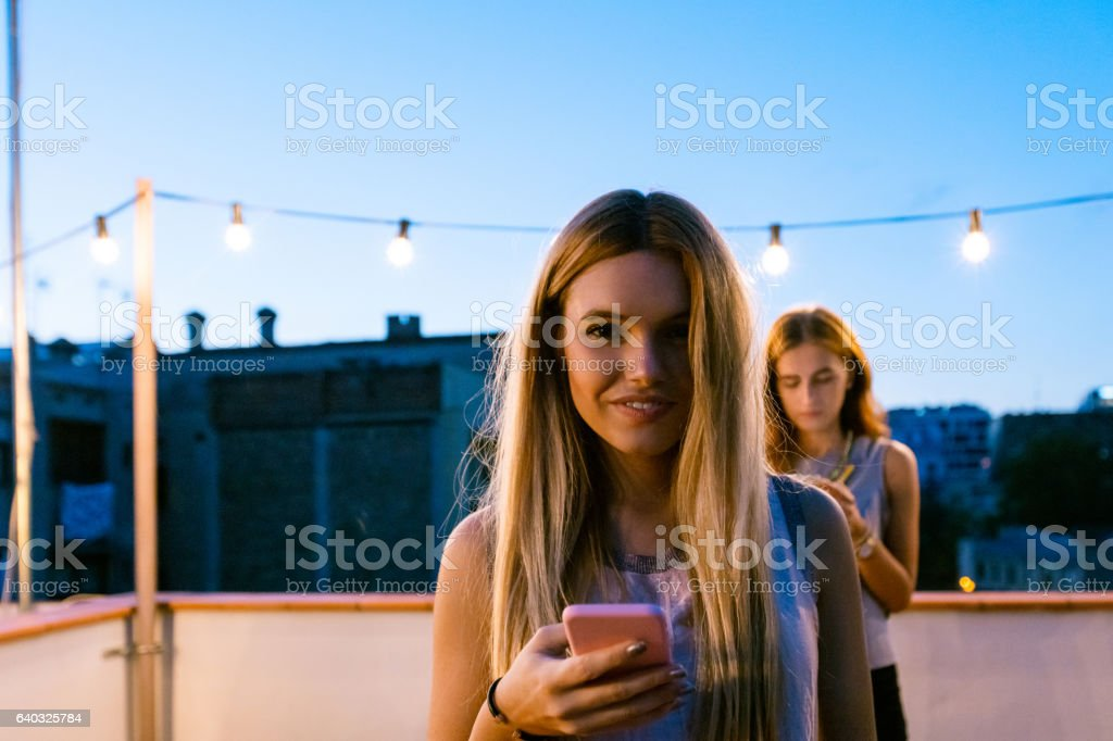 Young woman using smart phone at the rooftop party stock photo