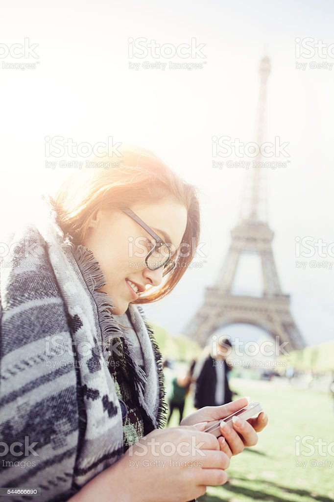 Young woman using smart phone in front of Eiffel tower stock photo