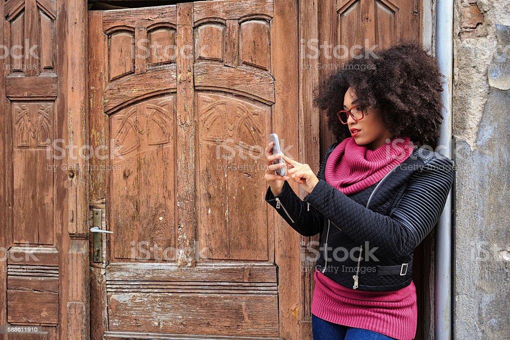 Young woman using smart phone in front of wooden door stock photo