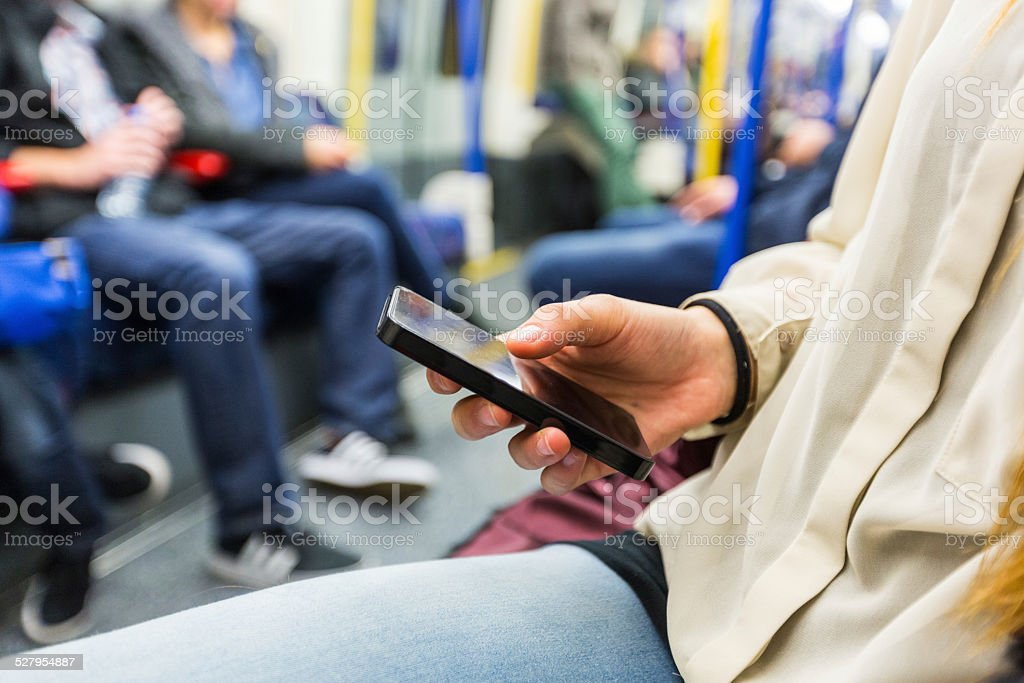 Young Woman Using Smart Phone in London Tube stock photo