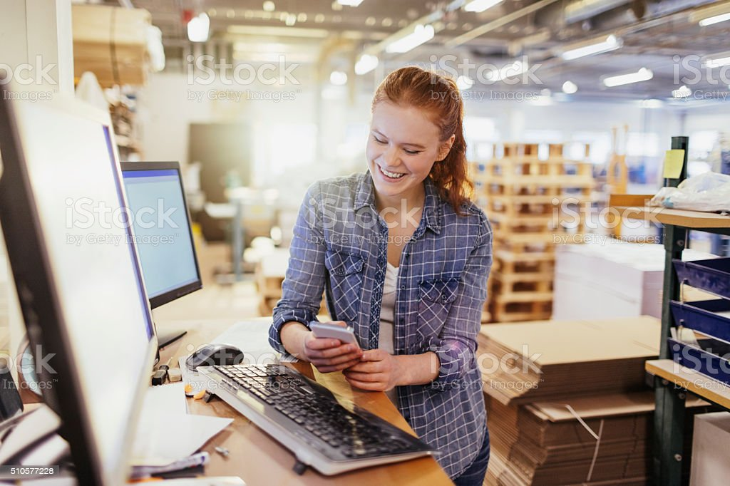 Young woman using smart phone in printing factory stock photo