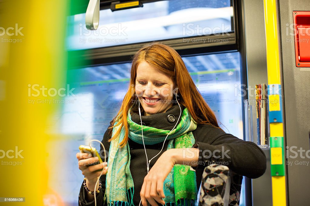 Young woman using smart phone in public transportation stock photo