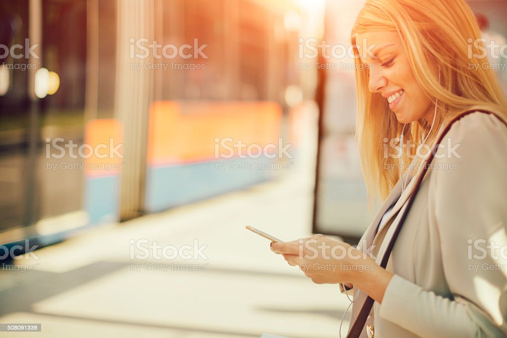Young Woman Using Smart Phone on Bus Station stock photo