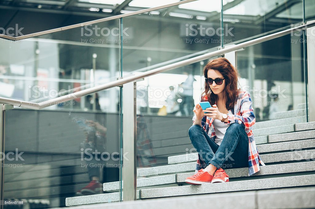 Young woman using smart phone on stairs stock photo
