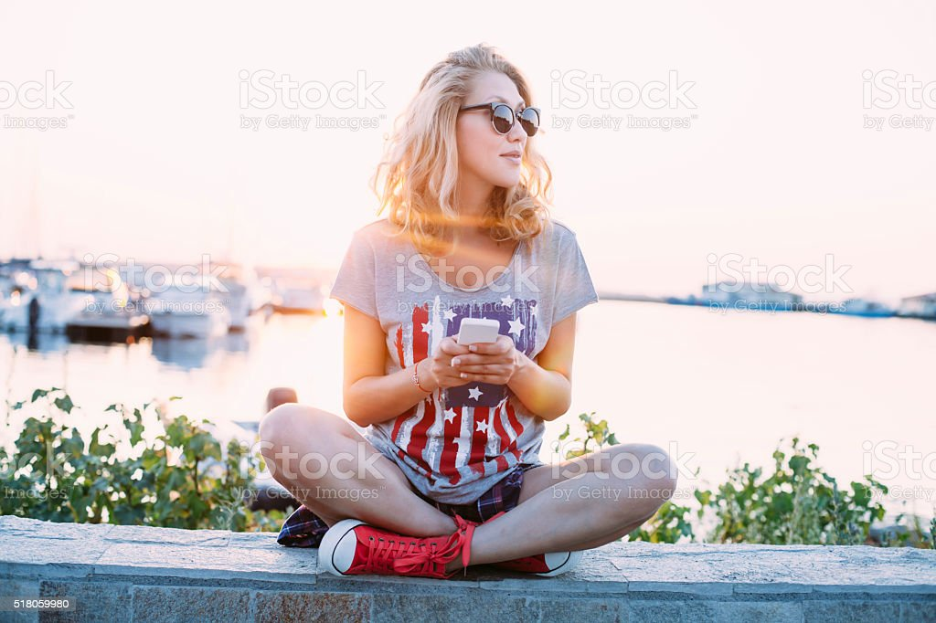 Young woman using smart phone on the beach stock photo